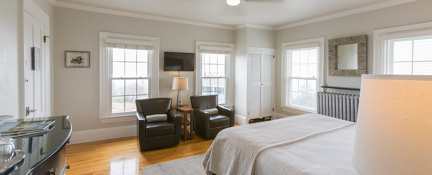 The many windows let plenty of sunshine into the spacious guest room, with two comfortable leather chairs to relax in