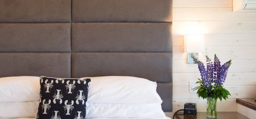 Enjoy the comfort of a luxury firm king mattress and custom headboard, giving this guest room a modern feel