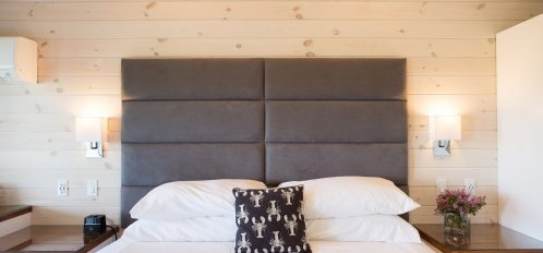 A king bed with a custom headboard, wood panel walls are featured in this modern guest room