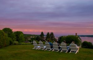 People sitting in chairs on the lawn at Topside Inn during sunset
