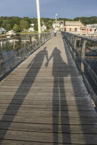 The shadows of two people holding hands on a bridge