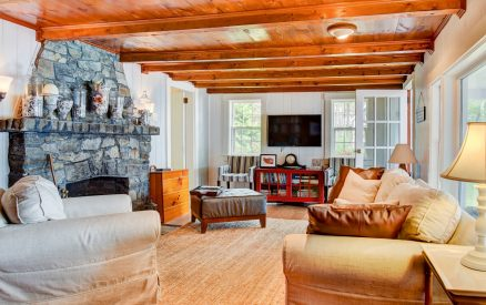 Spacious living room with ample and comfortable seating, and a beautiful stone fireplace