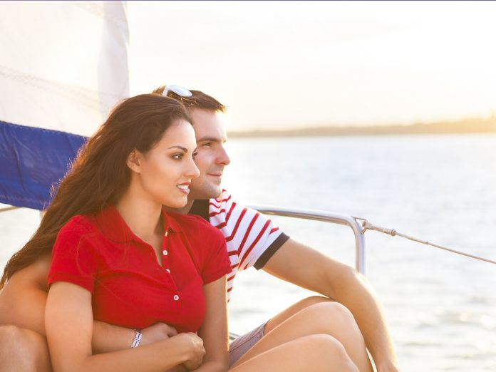 Young smiling couple on a boat enjoying romantic getaways in Maine