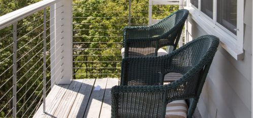 Covered sitting porch with comfortable seating to enjoy wonderful harbor views.