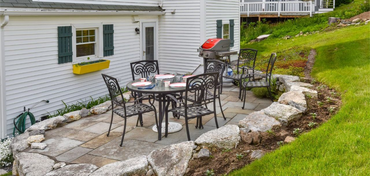 Outside stone patio dining area with six burner grill