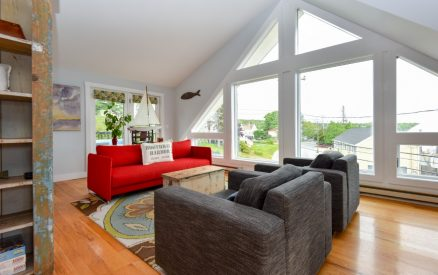 A comfortable living room with large bay windows looking towards the ocean