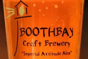 A glass of beer with the Boothbay Craft Brewery logo on it