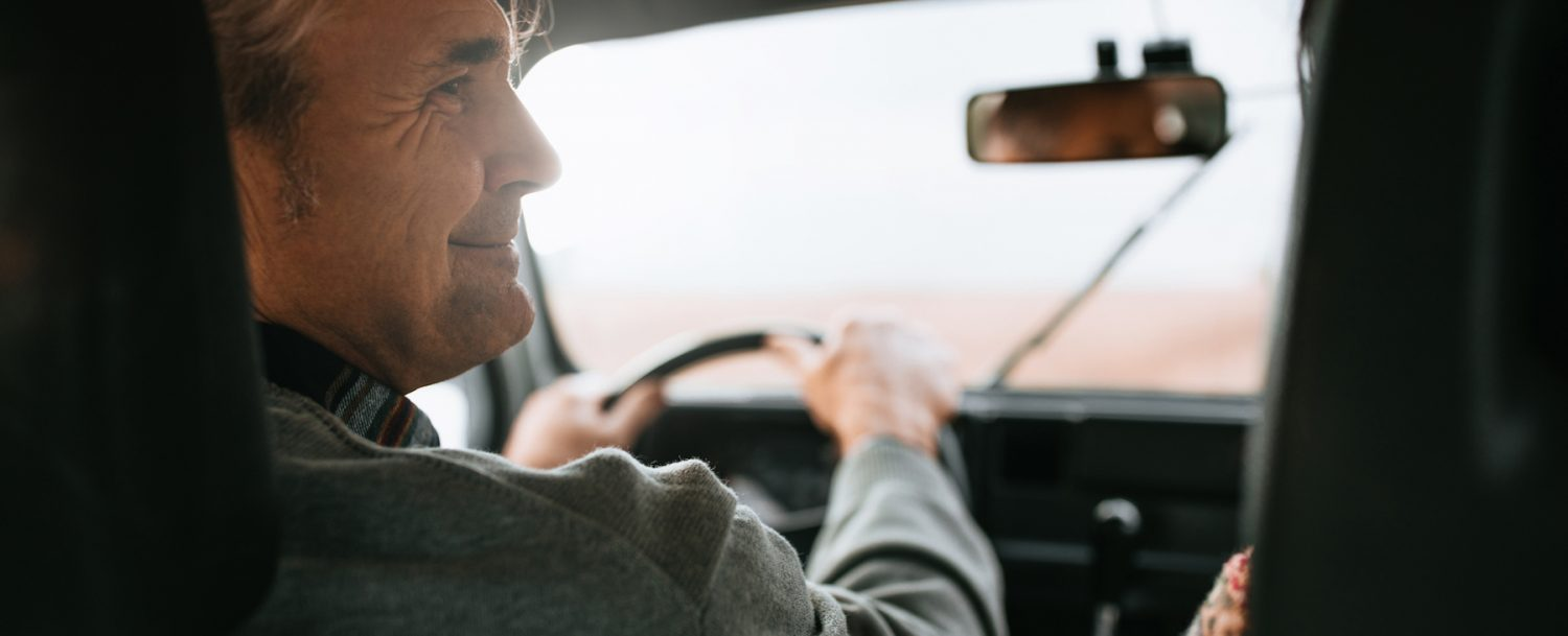 A man driving in his car during a Route 1 road trip