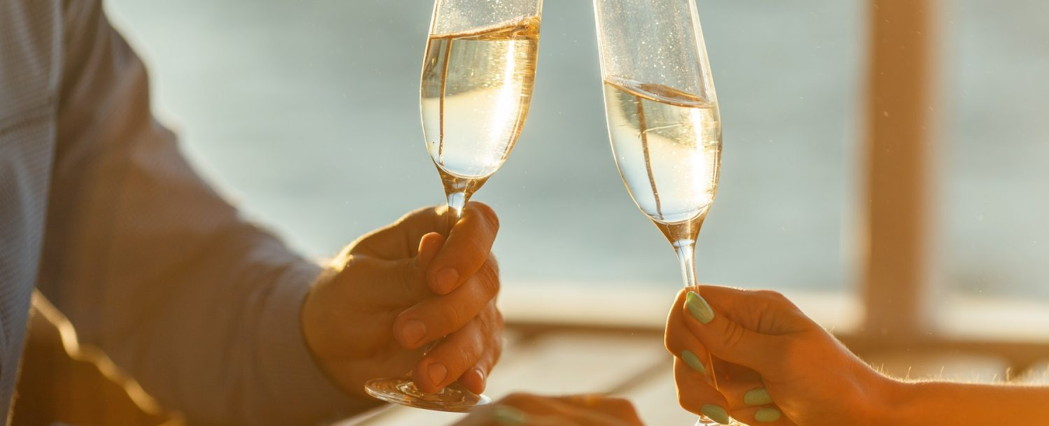 A man and woman with Champagne glasses on a romantic getaway in Maine