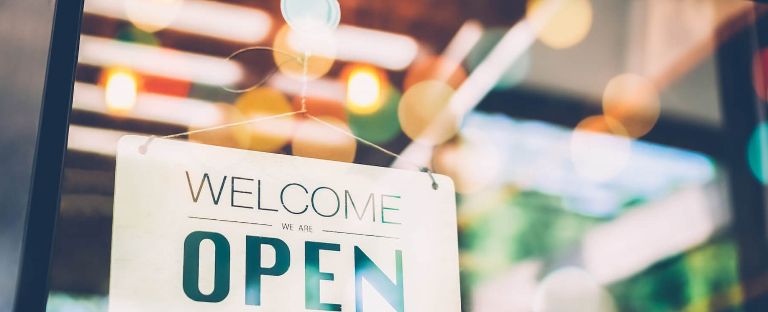"""A sign that says """"WELCOME: WE ARE OPEN"""""""